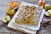 Vegan pumpkin and quark yeast dough strudel with apple and pear compote and oat and date crumbles on a wooden board
