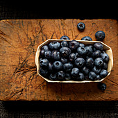 Blueberries in wooden tray on cutting board