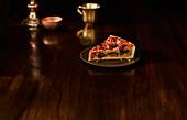 Mandel-Pflaumenkuchen mit Streuseln vor dunklem Hintergrund