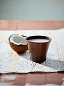 A cup of coconut milk and half a coconut milk