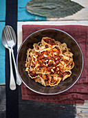 Tripoline with tomato sauce, anchovies, pine nuts, raisins and crispy crumbs (Italy)