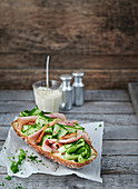 Baguette topped with cucumber and bacon on greaseproof paper