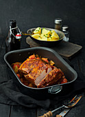 Roast pork in baking tin with parsley potatoes