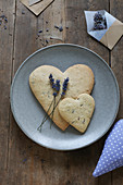 A heart-shaped, gluten-free lavender shortbread biscuit on a plate