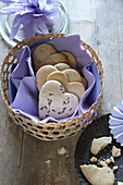 Heart-shaped, gluten-free lavender shortbread biscuits in a basket with a purple napkin