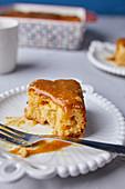 Angebissenes Stück Tres-Leches-Cake mit Karamellsauce und Meersalz
