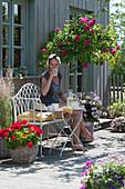 Terrasse mit Stammrose 'Heidi Klum', Geranien und Reitgras, Frau auf Bank genießt den Sommer