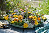 Kranz aus Ringelblumen, Schafgarbe, Salbei, Oreganoblüten und Wicke als Tischdekoration