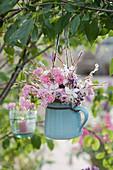 Romantischer Strauß aus Rosen, Prachtkerze und Oreganoblüten an Zweig gehängt