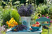 Lavendel - Strauß, Ringelblumen, Oreganoblüten und Schale mit Aprikosen und Wassermelone auf Tisch im Garten