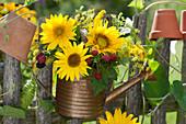 Strauß aus Sonnenblumen, Brombeeren, Fenchelblüten und Goldrute in Gießkanne am Gartenzaun