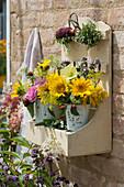 Wandhänger mit Sträußen aus Sonnenblumen, Goldrute, Stockrose, Rose, Malve, Fenchelblüten, Brombeeren und Katzenminze