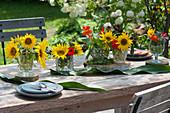 Kleine Sträuße mit Sonnenblumen und Kapuzinerkresse als Tischdekoration