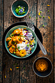 Butter chicken with yoghurt and edible flowers