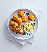 Potato and salmon balls with turmeric-yoghurt sauce