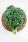 Curly kale leaves on a wooden plate
