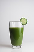 A glass of fresh green juice with a slice of cucumber