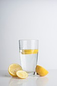 A glass of water with fresh lemon slices
