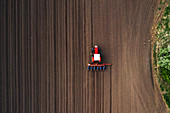 Aerial view of tractor sowing corn in field