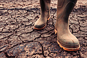 Farmer in rubber boots standing on dry soil
