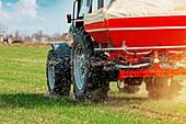 Tractor fertilizing wheat crop field with NPK