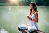 Woman meditating by a lake