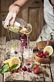 Flavoured Water mit Beeren, Zitrone und Eiswürfeln