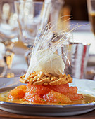 A grapefruit with vanilla ice cream and sugar strands