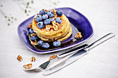 American pancakes with walnuts, blue berries and honey