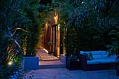 Holzverkleidetes modernes Garten- und Gästehaus bei Abendbeleuchtung