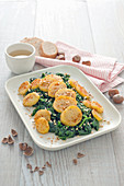 Spinach with fried pepper potatoes and chopped hazelnuts
