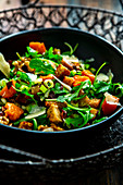An autumnal salad with caramelised pumpkin, rocket, walnuts, bacon and croutons