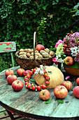 Herbstdeko mit Äpfeln, Walnüssen, Kürbis und Herbststrauß