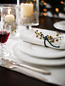 White place setting decorated for winter with a berry branch