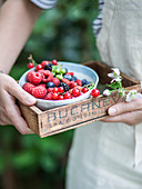 Woman holds bowl of fresh berries in wooden box