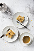 Gluten-free blondie with hazelnut served on white plates with coffee