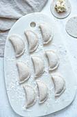 Gluten-fee uncooked dumplings ruskie served on marble board