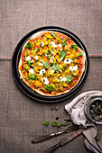 Vegan spelt pizza with grated pumpkin, courgette, lamb's lettuce and pumpkin seeds
