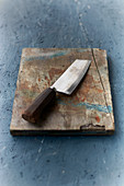 A chef's knife on a wooden board