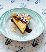 A piece of cheesecake with chocolate sauce