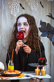 Verkleidetes Mädchen isst Karamellapfel zu Halloween
