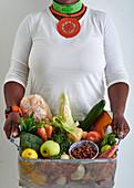 Frau hält Korb mit Gemüse, Obst und Lebensmitteln