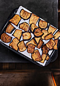 Fried aubergine slices on a baking tray