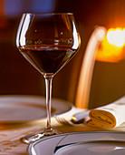 Rotweinglas neben Teller