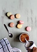 Person pouring milk into cup of coffee near bunch of colorful macaroons and spoon with napkin
