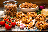 Different kinds of pasta, garlic, tomatoes and parmesan cheese