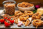 Verschiedene Nudelsorten, Knoblauch, Tomaten und Parmesan