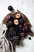 Autumn fruits: red grapes, blackberries and plums on a wooden board