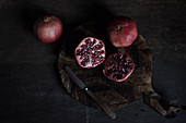 Pomegranates, whole and halved on a dark background