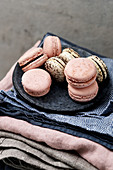 Two kinds of macarons on plates and stacked tablecloths